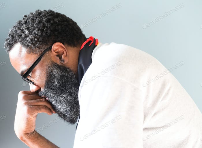 Bearded black man with glasses deep in thought.