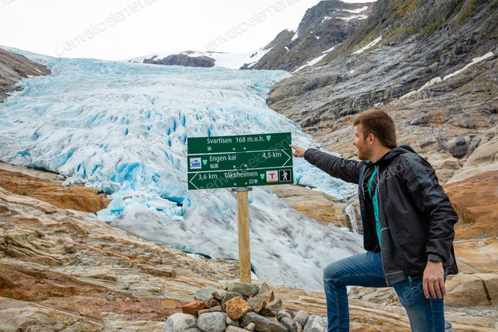 Young man next to pointer to glacier