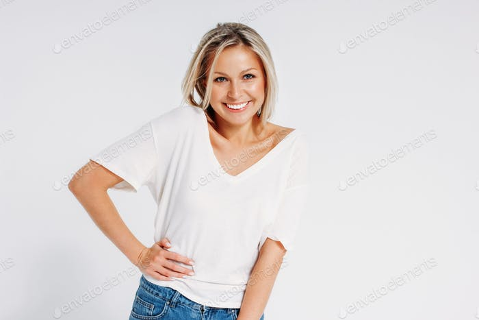 Charming friendly blonde smiling woman 35 year in white t-shirt and blue jeans looking at camera