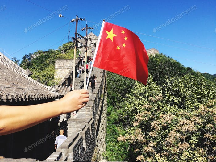 Hand holding flag of China in the Great Wall of China