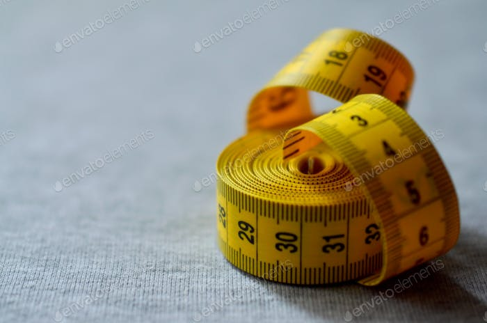 Yellow measuring tape with numerical indicators in the form of centimeters or inches lies on a gray