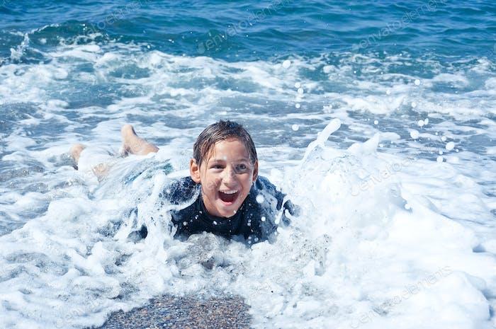 Kinder spielen mit Meereswellen im Badeanzug
