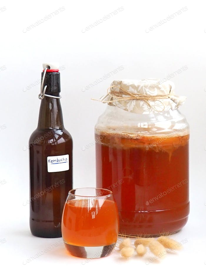 Kombucha, a healthy home-made carbonated drink, jar, bottle and glass with drink on white background