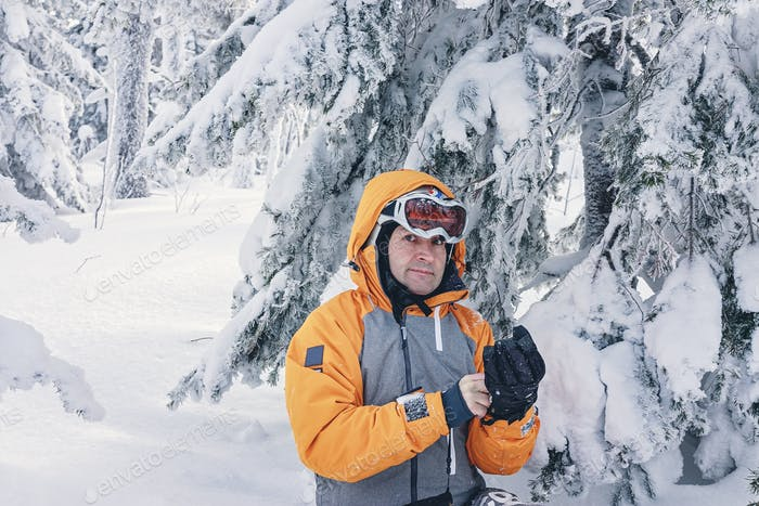 Portrait of a male snowboarder in bright suit in a sports helmet and ski goggles