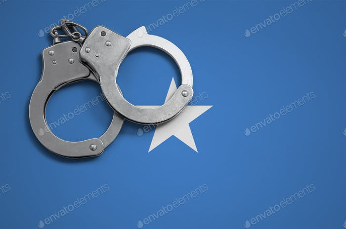 Somalia flag  and police handcuffs. The concept of crime and offenses in the country.