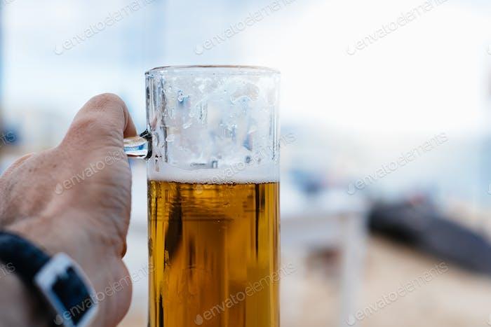 Hand des Mannes hält ein Pint kaltes Bier vor verschwommenem Sommerhintergrund