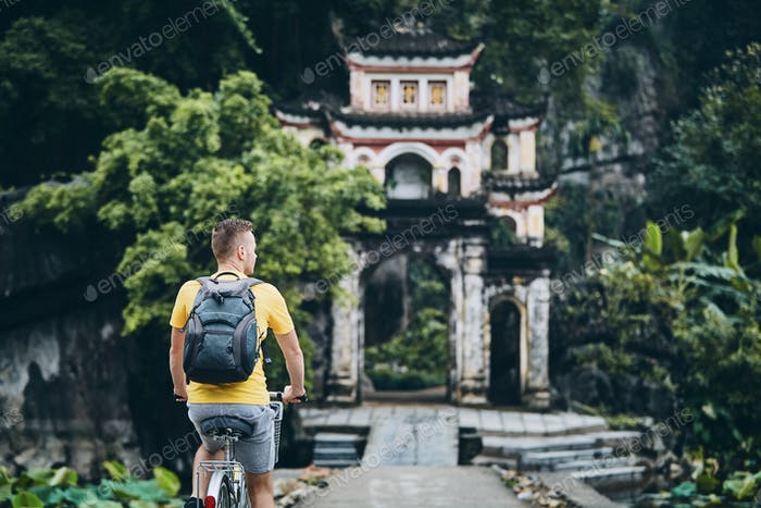 Trip by bike. Man with backpack bicycling on road to Buddhist temple in Ninh Binh province, Vietnam.