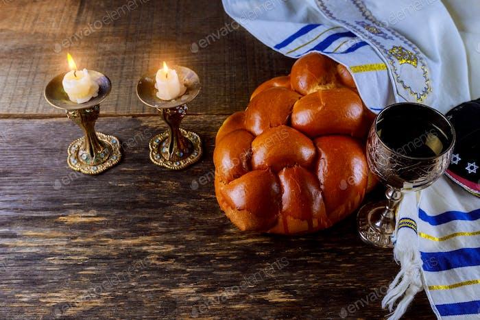 Shabbat Eve Tisch mit gedecktem Challah-Brot, Kerzen und einer Tasse Wein.