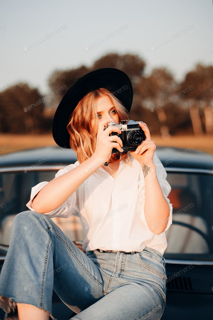 Pretty girl in white shirt and flared jeans with old photo camera is sitting on vintage car's hood.