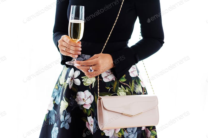 Woman wearing a beautiful and elegant dress, holding a champagne glass, luxury style, well dressed