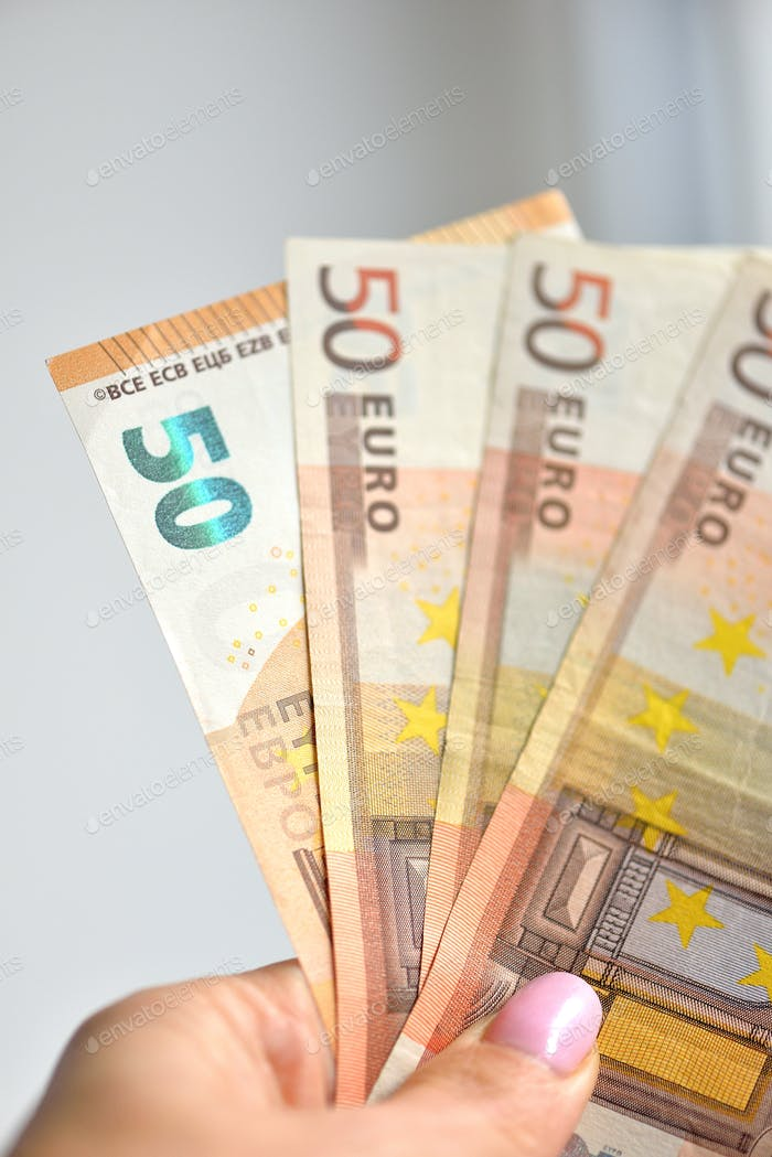 Hand holding 50 banknotes money (EUR), currency of European Union.