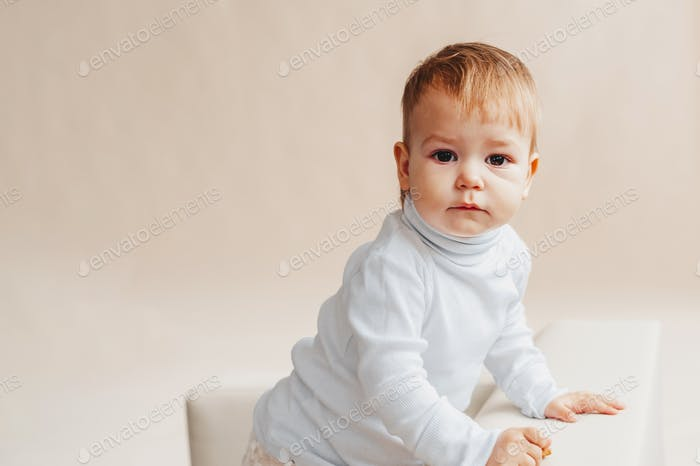 Portrait of a lovely baby in gentle colors. Little girl looking at the camera
