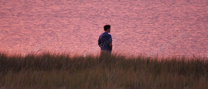 Teenage boy at sunset standing at the edge of a marshlands in pockets looking out onto the water..