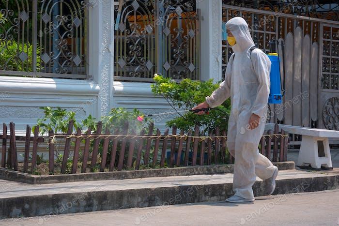 Desinfektionsmittel Arbeiter in Schutzanzügen mit Maske Sprühen Desinfektionsmittel Chemikalie in der Community