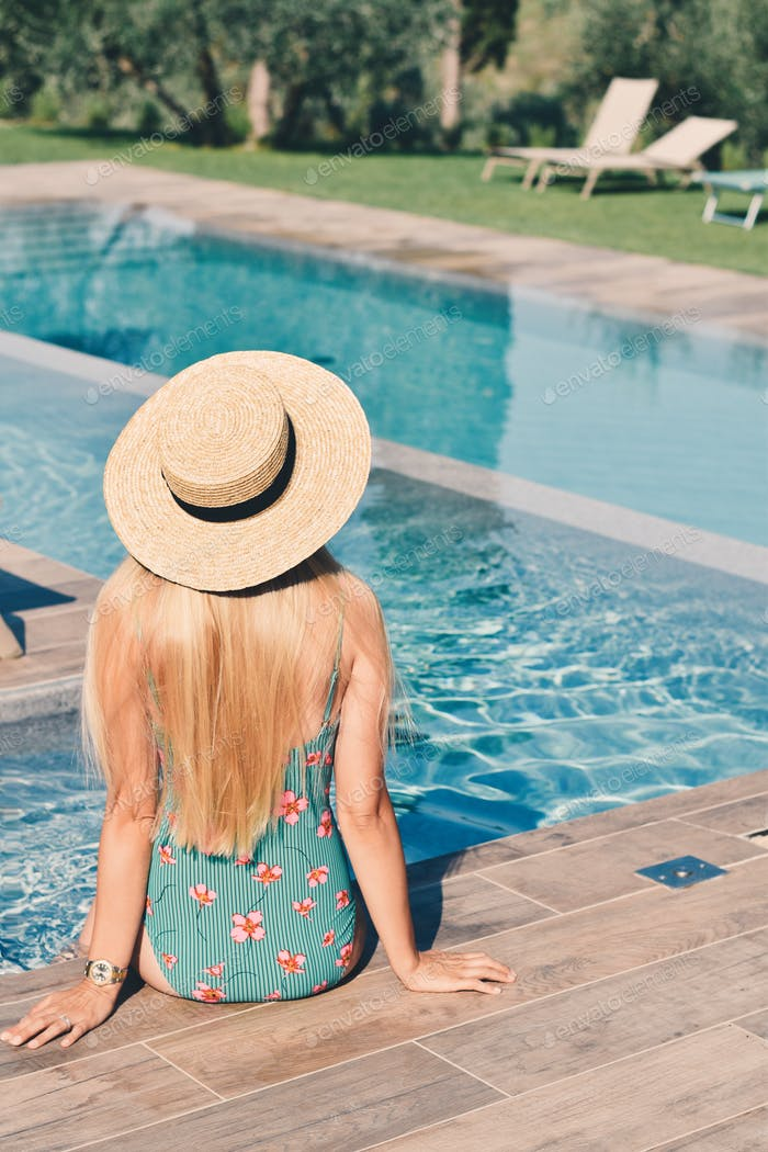 Rear view of woman in bathing suit sitting at the poolside