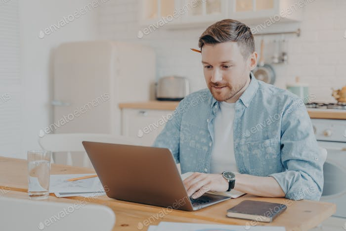 Focused young man freelancer using laptop while sitting at kitchen table
