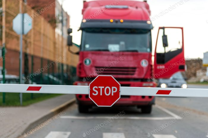 Truck standing at the barrier with a STOP sign.