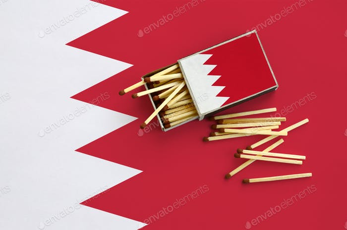 Bahrain flag  is shown on an open matchbox, from which several matches fall and lies on a large flag