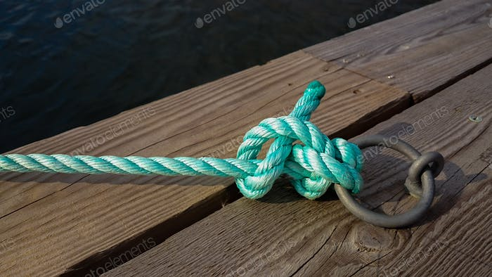 Green knot mooring for the boat in the harbour, reminder symbolic, diagonal, focus