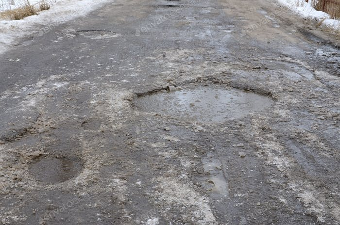 Damaged asphalt road with potholes caused by freezing and thawing cycles during the winter