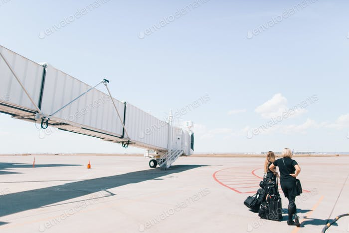 Flight attendants wait for plane to arrive on the tarmac on a bright and sunny day