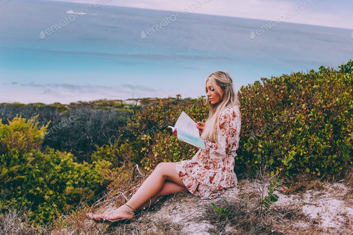 Woman with long hair reading a book outdoors