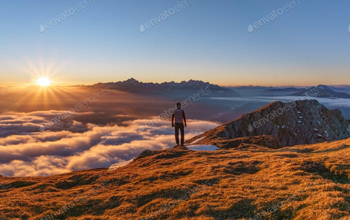 Hiker at the top of the mountain at Sunset. Beautiful view of Julian Alps.