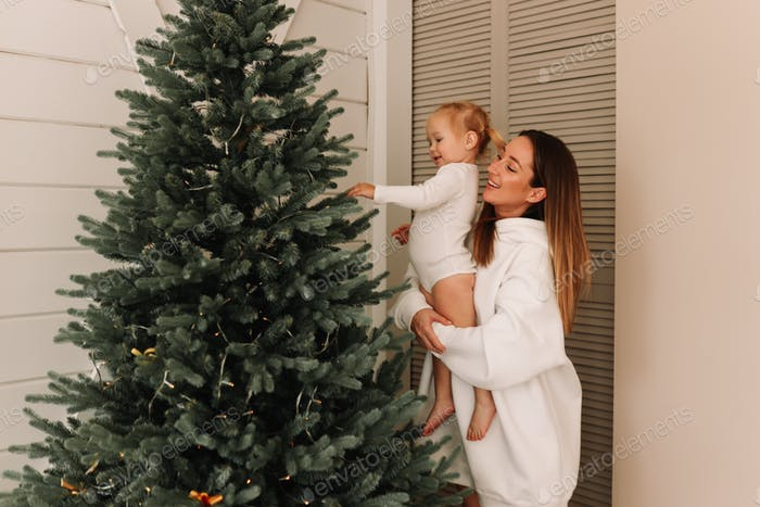 Mom and little daughter child decorate the Christmas tree together at home