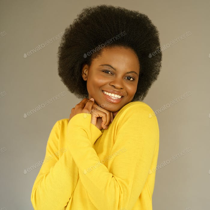 Happy Afro American millennial woman with afro hair style wear yellow sweater posing over grey wall