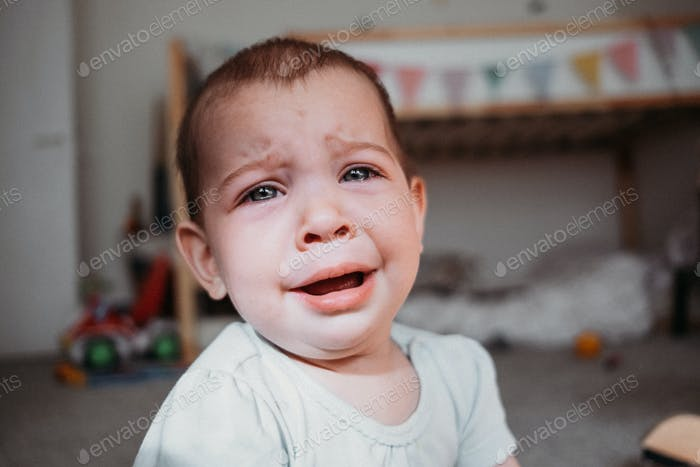 Infant baby crying in nursery at home. Eyes full of tears