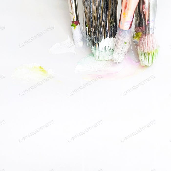 Minimalist shot of dirty paintbrushes with wet paint in light pastel shades on a stained white