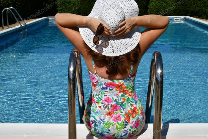 Middle-aged woman active Gen X full-figured female wearing swimsuit floppy hat and sunglasses