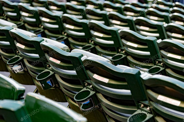 Empty stadium bleacher seats from behind with cup holders