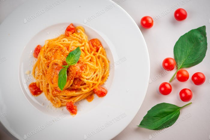 Pasta with tomatoes and basil, White plate.