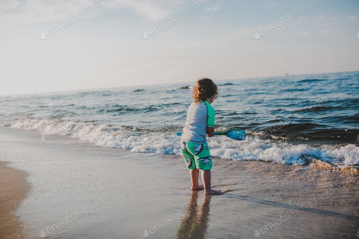 Toddler boy on shoreline of beach on vacation