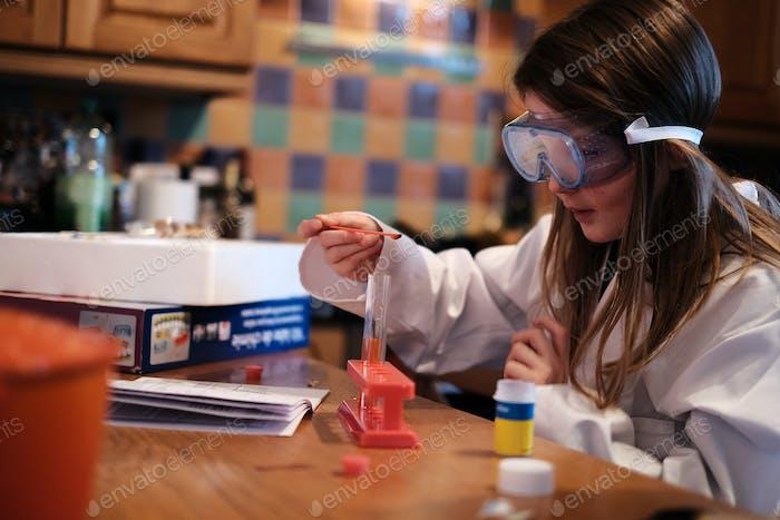 Ein Mädchen, das in einem weißen Labormantel und einer Schutzbrille gekleidet ist, legt Chemikalien in ein Reagenzglas