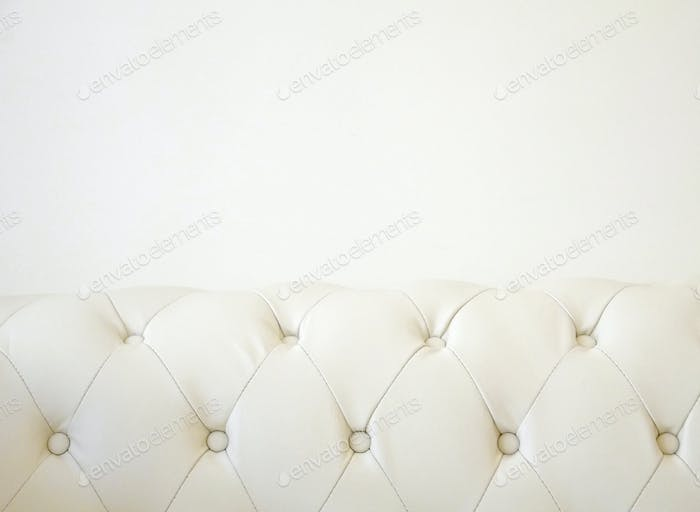 Cream studded sofa on a cream wall background