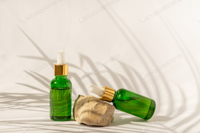 green glass serum bottles with dropper on white background. Assortment of unbranded products