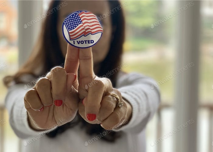 Latino woman holding an I VOTED sticker. It's imperative to exercise our duty & right as citizens.