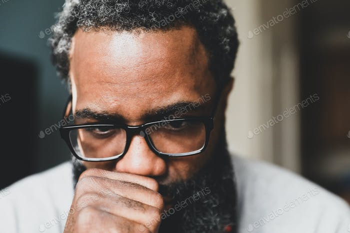 A bearded man with glasses deep in thought