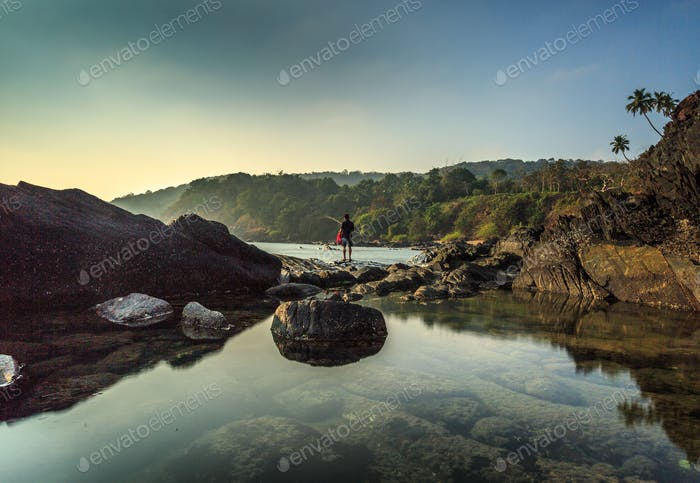 man is fishing standing on rocks , tiny humans in big world