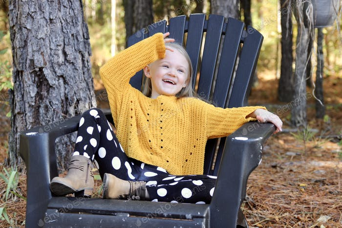 A little girl in fall clothing having fun posing in a chair in the woods.