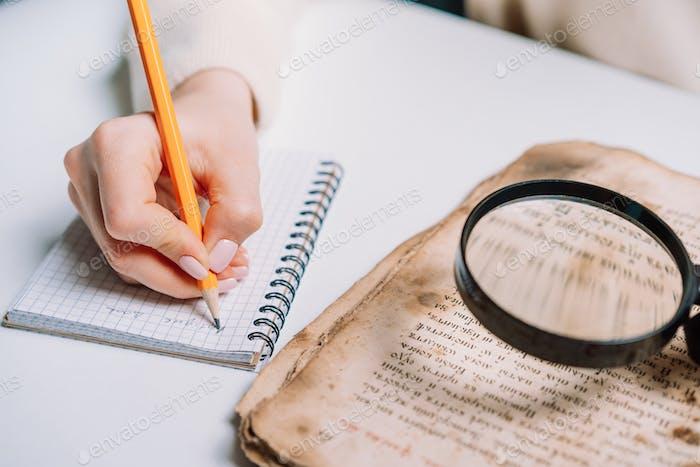 Forscher untersucht ein antikes Buch mit Lupe. Wissenschaftliche Übersetzung von antiken Literatur