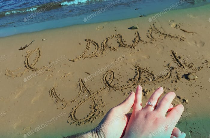 Engagement announcement written in the sand
