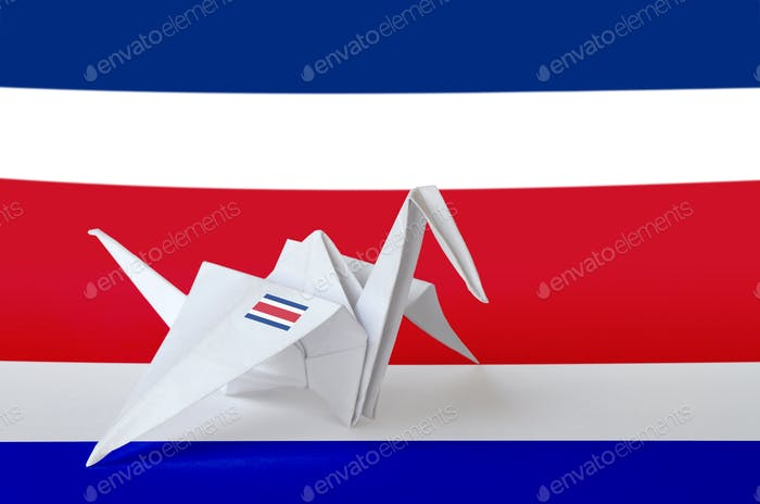 Costa Rica flag depicted on paper origami crane wing. Oriental handmade arts concept