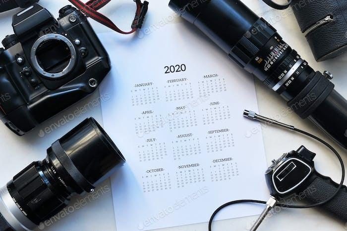 Kalender und Fotokamera auf einem weißen Tisch