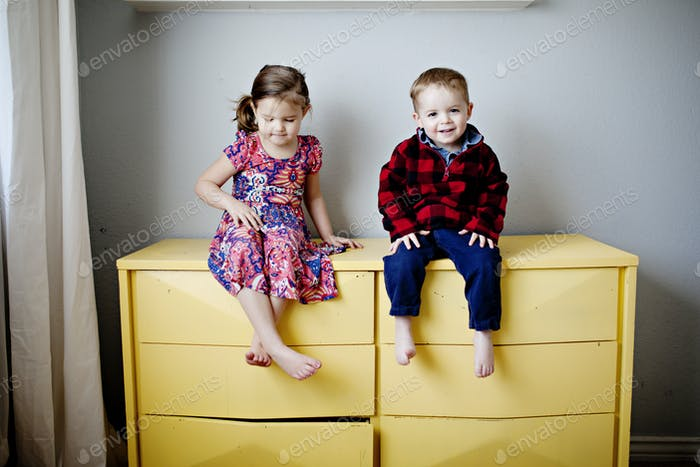 two kids sitting on a yellow dresser