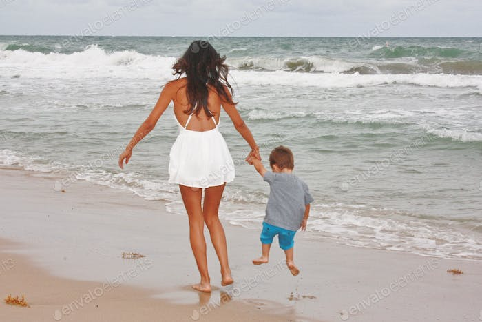 Mother and son running along the shoreline