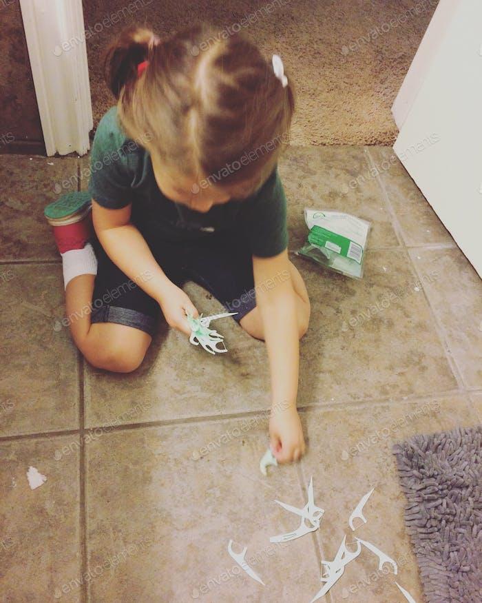 Kleines Mädchen, das verschüttete Zahnseide im Badezimmerboden aufräumt
