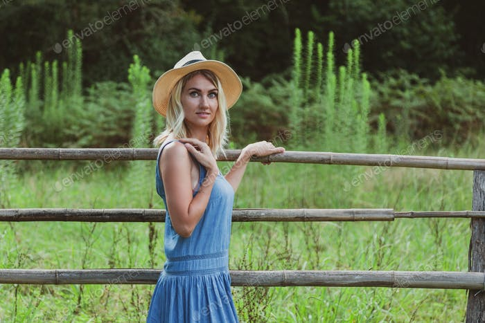 Young woman in a straw hat on nature near a wooden fence in the village